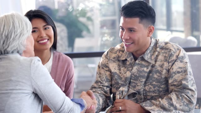 Army soldier greets mental health professional Young Hispanic military soldier shakes hands as he greets a senior Caucasian female mental health professional. The soldier smiles as they discuss the improvement he has made since staring therapy. The soldier's wife is sitting next to him. veteran stock videos & royalty-free footage