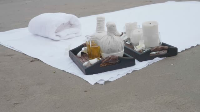 vídeos de stock e filmes b-roll de aroma oil and massage set on the beach - oleo palma