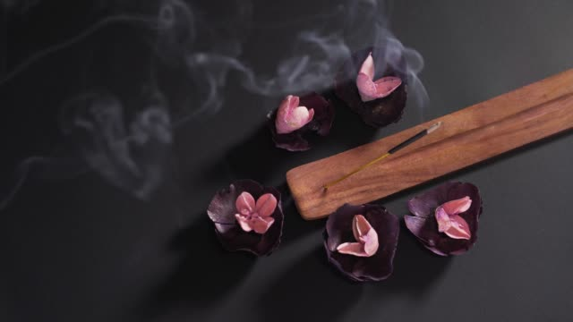 Aromatic religious stick on a black background in a wooden stand. Dry fragrant soothing flowers in the spa. The concept of zen and meditation 4k