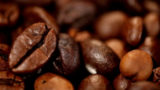 Aromatic roasted coffee beans lying on sack, energy boosting morning drink video
