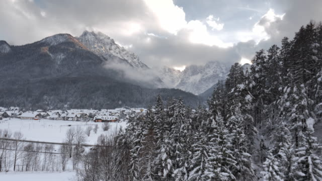 AERIAL Around the hill into an alpine snow covered valley video