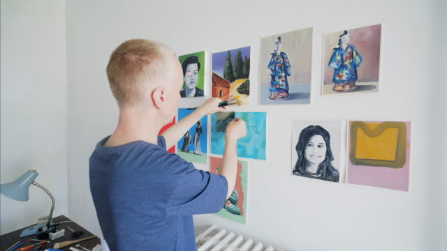 Arranging paintings symmetrically on the wall. video