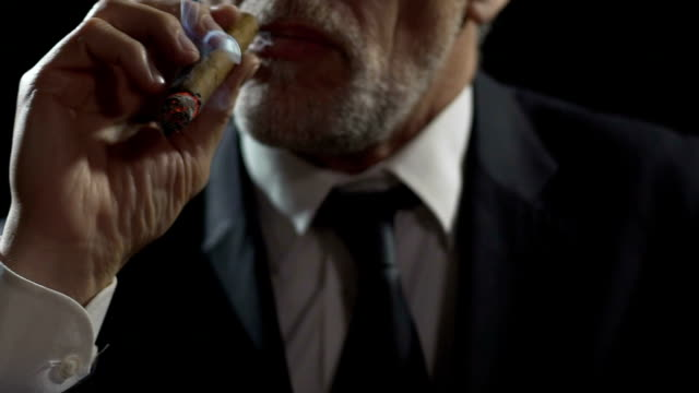Arrogant gangster smoking expensive Cuban cigar, dangerous mafia, slow-motion video
