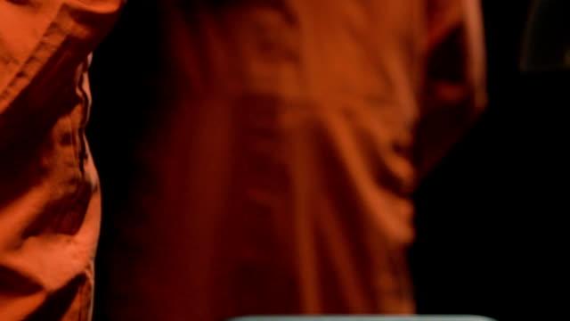 Arrogant prisoner walking into interrogation room, examining mirror reflection