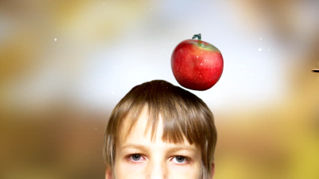 Arrow capturing red apple from head. Colorful background. video