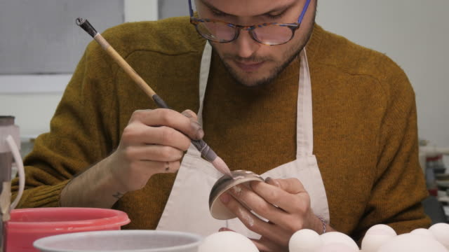 Art Studio. Young Man Painting Porcelain Cup in Art Studio. video