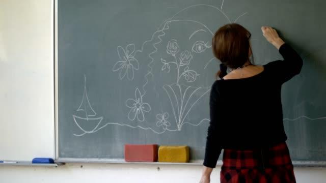 Art teacher is drawing on blackboard