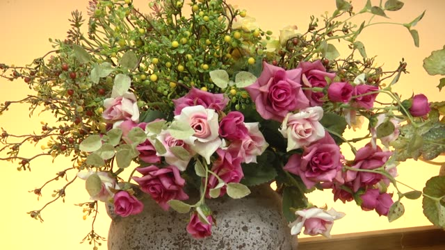 Artificial flowers bouquet in the vase. flower vase with beautiful red flowers. Bouquet of roses artificial flowers