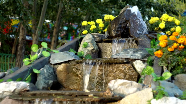 Artificial waterfall in the park, water runs along the stone steps