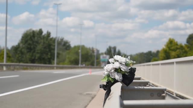stockvideo's en b-roll-footage met kunstmatige witte rozen bloemen op de site van een auto-ongeluk verkeersongeval op de brug veiligheid metalen hek met een fatale uitkomst - floral line