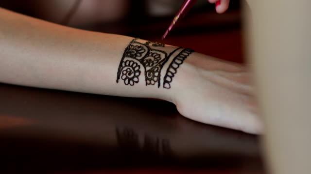 Artist applying henna tattoo on bride's hands. 4K video