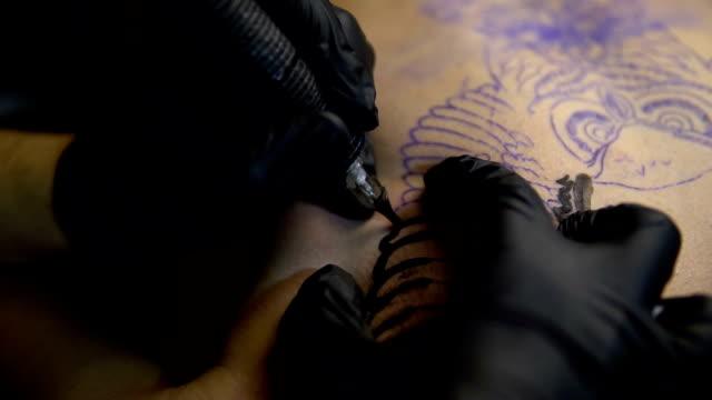 artist draws a tattoo on the chest of a man close-up - tatuaż filmów i materiałów b-roll