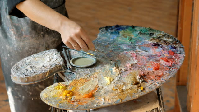 artist in dirty apron mixes oil paints on palette in studio - imperfection stock videos & royalty-free footage