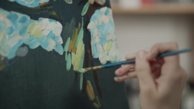 Artist is applying strokes of oil paint on canvas, close-up