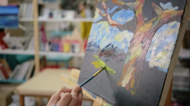 Artist is applying yellow gouache on black canvas in art school, close up