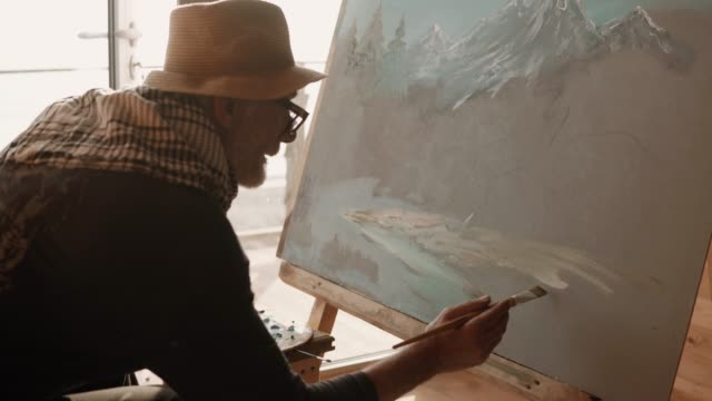 artist is engaged in drawing oil paints by brush on canvas which stands on easel - vídeo