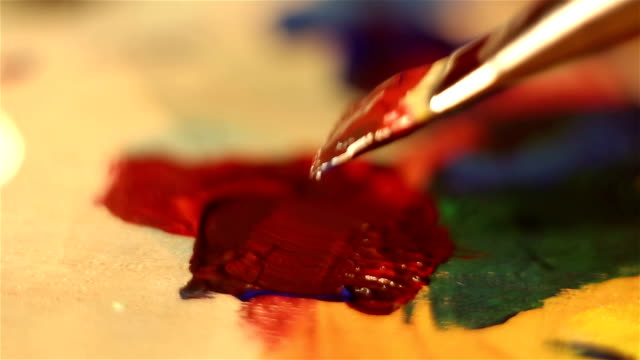 artist lowers the brush in red paint and mixes it on the palette. - cavalletto attrezzatura per arti e mestieri video stock e b–roll