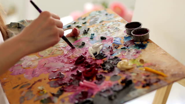 Artist mixes paint on palette with a brush,closeup video