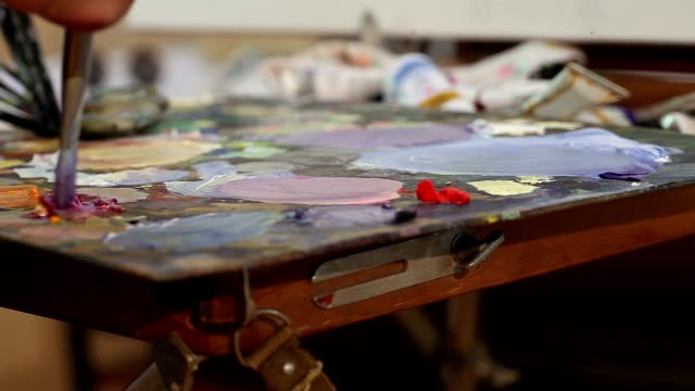 Artist mixes paint on the palette, Art brush mixed paint on the palette, artist brush mix color oil painting on palette, artistic brush, hand close-up video