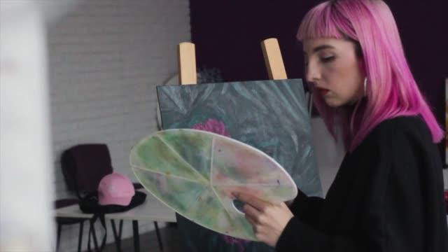stockvideo's en b-roll-footage met kunstenaar mengt verf op het palet voor het schilderen van een foto, schilder in de studio, schepper maakt kunstwerk - roze haar