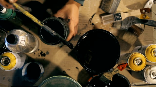 Artist open can with pain and stir it up and pour in another can video