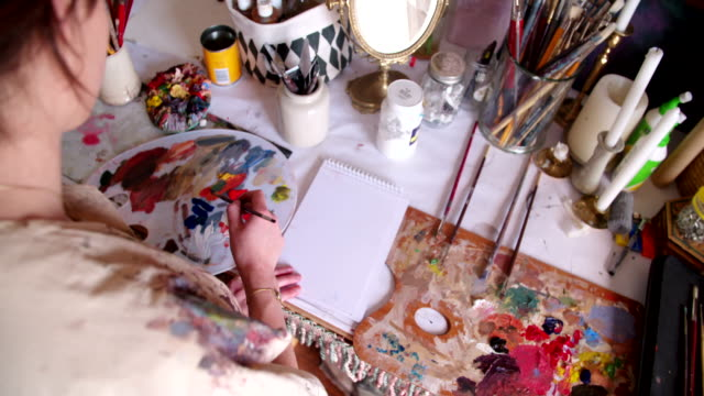 Artist painting on paper with a palette and bright colors video