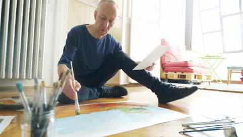 vídeos de stock e filmes b-roll de artist painting while sitting on the floor. - arte