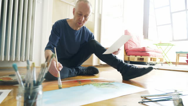 Artist painting while sitting on the floor. Mature artist spending his day in the art studio. To feel more comfortable, he decides to continue his masterpiece on the floor. hobbies stock videos & royalty-free footage
