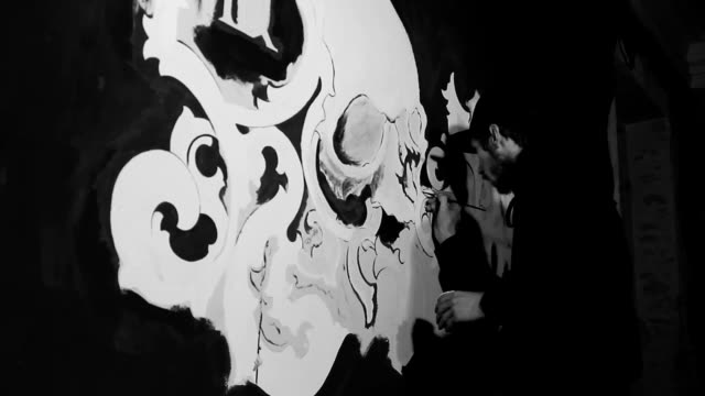 Artist painting white grafiti with skull on the black wall