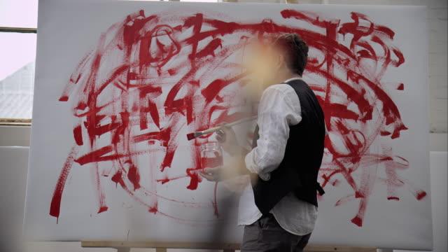 vídeos y material grabado en eventos de stock de artista de la pintura sobre lienzo con color rojo - pintor artista