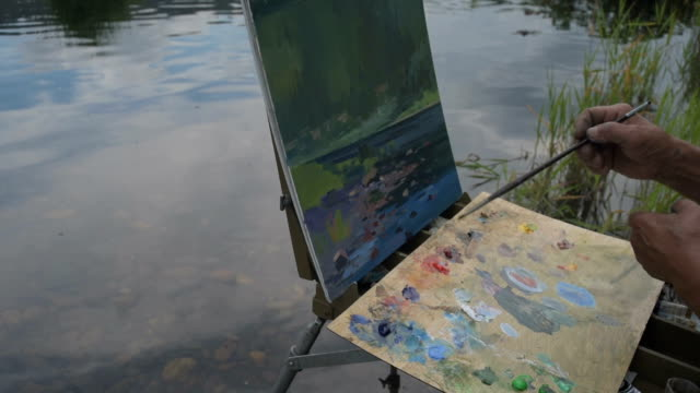 Artist river nature Old artist paints a picture on the shores of a wild river in Siberia, Russia. mural stock videos & royalty-free footage