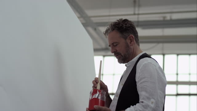 Artist starts painting with red color on canvas video
