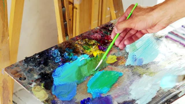 stockvideo's en b-roll-footage met kunstenaar roert kwast alvorens schilderij - fresh start yellow