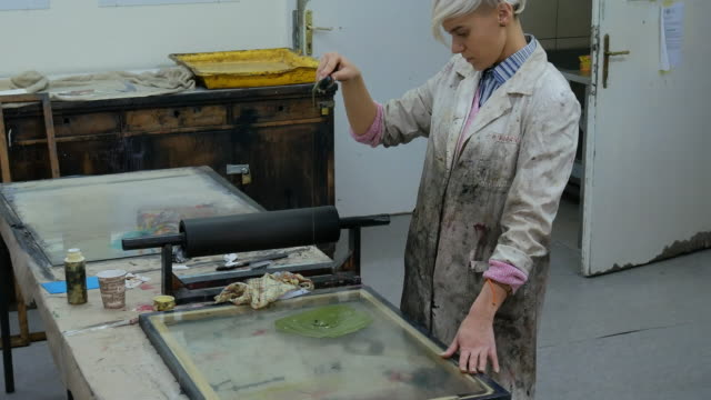artist working in her workshop with intaglio printing - литография стоковые видео и кадры b-roll