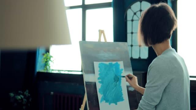 vidéos et rushes de l'artiste travaille dans un atelier lumineux. la fille fait des croquis avec un pinceau avec des peintures. mouvement latéral de la caméra. - toile à peindre