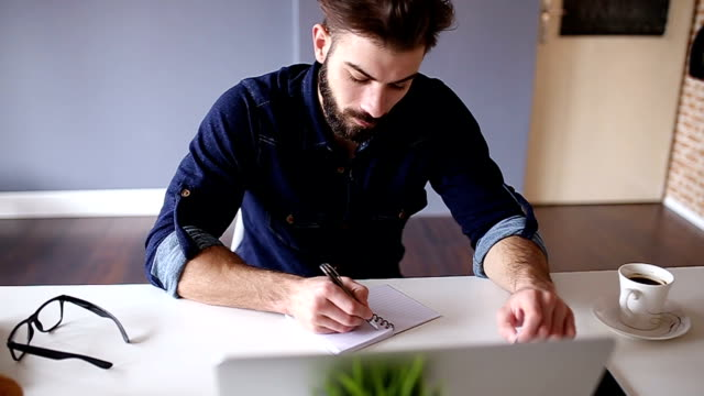 Artist writing list of things he needs to buy video