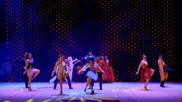 stockvideo's en b-roll-footage met artistieke mensen dragen kostuums van de schilderachtige dansen op het kleurrijke podium - vetschmink