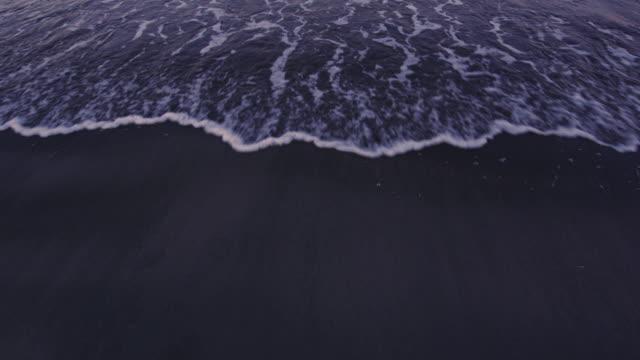 vídeos y material grabado en eventos de stock de toma artística de pov de una marea entrante en una playa al atardecer. video original de color común disparo en 6k por una cámara de red dragon. - marea