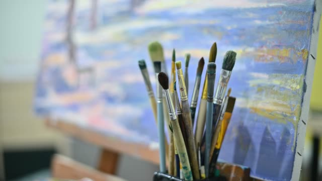 artist's brushes on the background of a painting with an easel - cavalletto attrezzatura per arti e mestieri video stock e b–roll