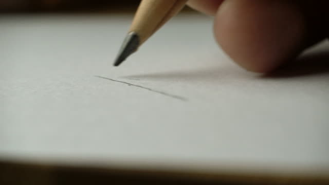 Artists hands drawing wooden pencil writes on paper