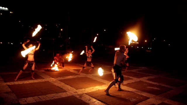Artists in ancient dress demonstrate fire show during rain. video