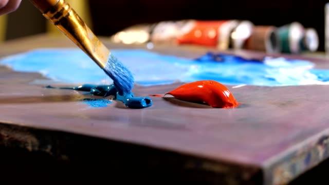 tavolozza dell'artista. splendidamente c'è una vernice diversa. mano femminile con un pennello quadrante il colore desiderato. mo lento 4k - tavolozza video stock e b–roll