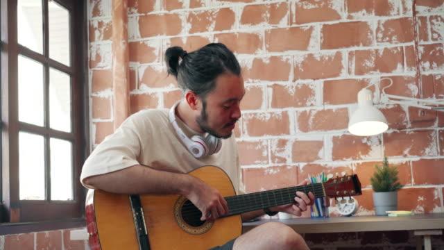 自宅のサウンドスタジオで音楽を制作するアーティスト、ギターを弾くアジア人男性、自宅のリビングルームで歌うアーティスト。ライフスタイルの男は、自宅のコンセプトで朝にリラック� - スタジオ 日本人点の映像素材/bロール