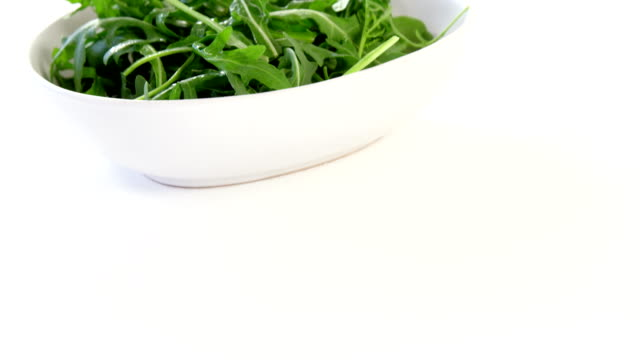 Arugula in bowl Arugula in bowl against white background salad bowl stock videos & royalty-free footage