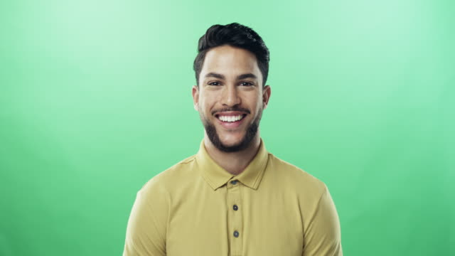 As confident as he is handsome 4k video footage of a confident young man posing against a green studio background background color stock videos & royalty-free footage