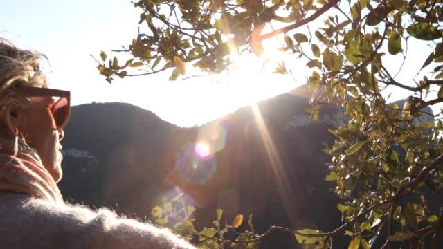 vídeos de stock e filmes b-roll de pov as female hiker walks along trail at sunrise - 55 59 anos