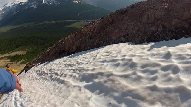 POV as hikers descend snow slope while boot skiing
