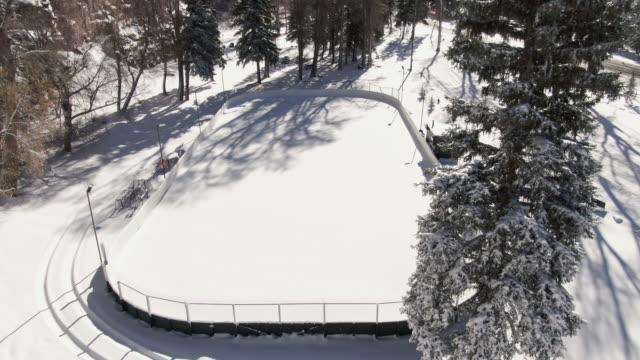 vidéos et rushes de croissant de drone aérien shot d'une petit enneigé patinoire extérieure entourée de pins enneigés sur une lumineuse journée d'hiver - hockey sur glace