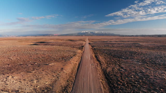 vídeos de stock e filmes b-roll de ascending aerial drone shot of a vanishing point dirt road with mountains in the background outside of moab, utah with desert plains on either side underneath a blue sky at sunset/sunrise - estrada em terra batida