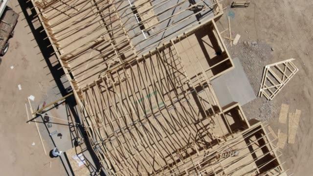 vídeos y material grabado en eventos de stock de ascendente aérea drone tiro de trabajadores de la construcción caminando a través de una casa que están enmarcando en un día soleado - imperfección